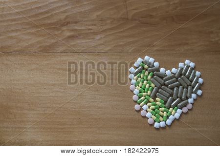 Pills and vitamins on the wood background close up
