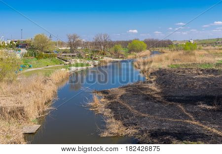 Sura river with burnt riverside at early spring season near Dnepr city Ukraine