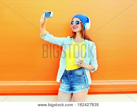 Fashion Pretty Woman Is Taking A Picture Self Portrait On A Smartphone Over Colorful Orange Backgrou