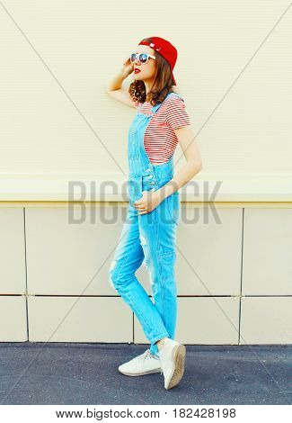Fashion Young Pretty Woman Wearing A Denim Jumpsuit In Profile Over White Background