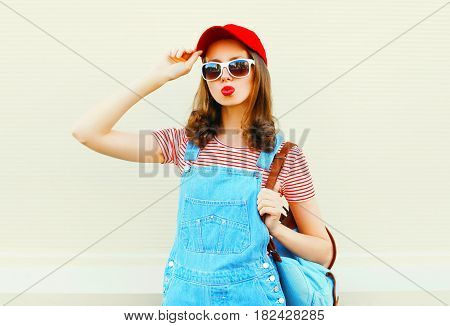 Fashion Young Pretty Woman Wearing A Denim Jumpsuit With Baseball Cap And Sunglasses Over White Back