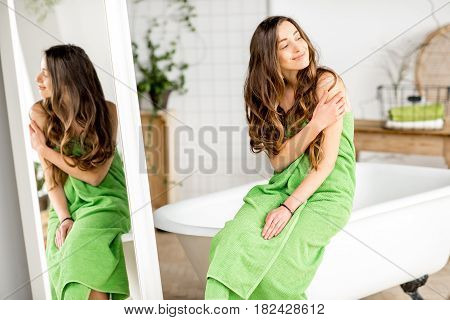 Portarit of a young woman in green towel relaxing on the bathtub at the comfortable bathroom