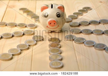 piggy bank and stacks of coins on wooden table. Financial and save money concept.