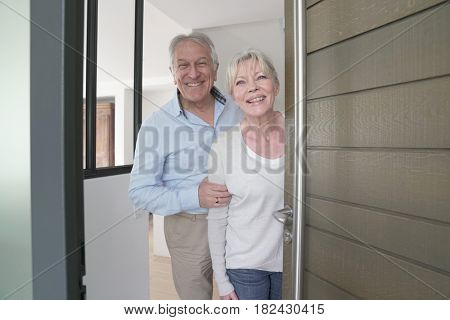 Senior people welcoming friends to enter home