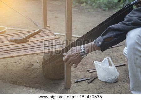 Man Sawing. sawing wood with selective and soft focus.