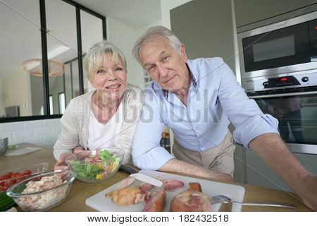 Senior couple cooking together in home kitchen