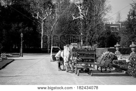 STRASBOURG FRANCE - APR 12 2016: Rear view of gardeners working near van with carriage trailer transporting toward destination new fresh flowers tree and bushes for the green spring park