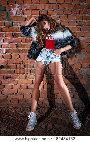Stylish Cool Cool Girl In Short Shorts With A Red T-shirt And Fur Coat, With Curly Long Hair Posing