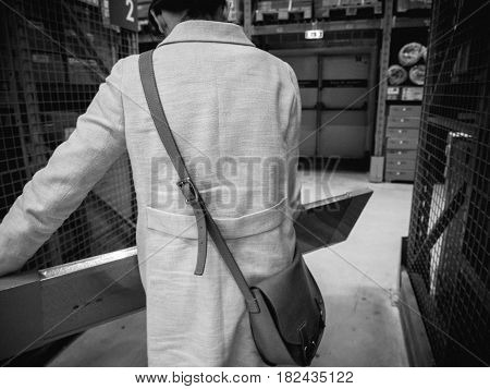 PARIS FRANCE - APR 10 2017: woman shopping with cart caddy inside IKEA store in the warehouse aisle area selecting the right object from the self-service rack black and white image
