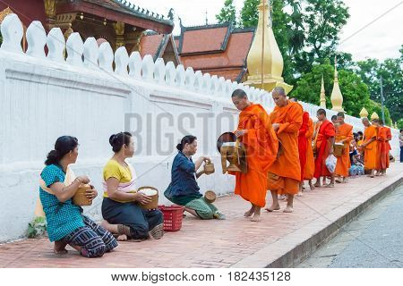 Luang Prabang, Laos - Jun 14 2015: Buddhist Alms Giving Ceremony In The Morning. The Tradition Of Gi