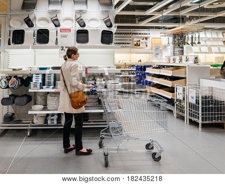 PARIS FRANCE - APR 10 2017: Single woman pulling caddy choosing dishes at the IKEA Shopping furniture store in Paris France. Being founded in Sweden in 1943 IKEA is the world's largest furniture retailer.