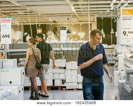 PARIS FRANCE - APR 10 2017: Happy couple buying laps and lighting equipment at IKEA Shopping furniture store in Paris France. Being founded in Sweden in 1943 IKEA is the world's largest furniture retailer.
