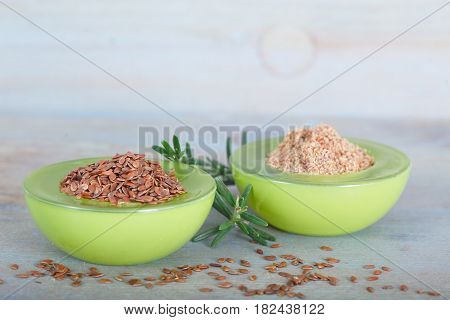 Whole and ground brown flax seeds or linseeds in green bowls