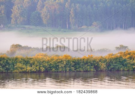 Autumn sunny landscape-view from height of autumn yellowed forest and autumn river with boat at early autumn morning. Autumn foggy landscape. Autumn nature background