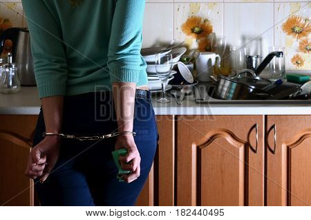 Fragment Of The Handcuffed Female Body At The Kitchen Counter, Filled With A Lot Of Unwashed Dishes
