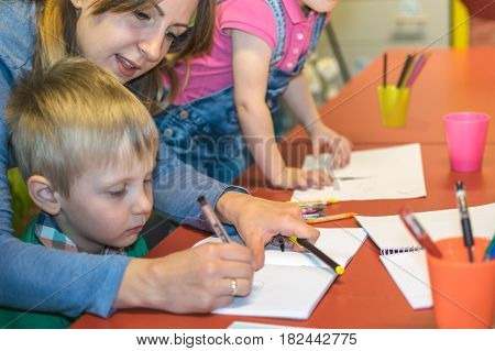 Teacher coloring with children in the kindergarten