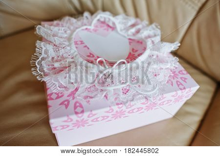 White Wedding Garter On Rose Box At Leather Sofa.