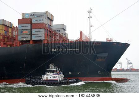 Oakland CA - April 18 2017: Tugboat REVOLUTION at the port side of cargo ship MAERSK EFFINGHAM assisting the vessel to maneuver into the Port of Oakland.