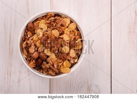 Top view of corn flakes and nuts in bowl on wood table