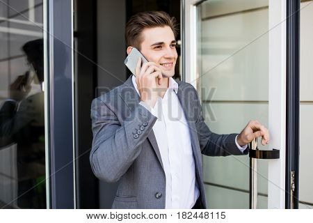 Young Business Man Speak On His Phone Near A Glass Door In Office Building