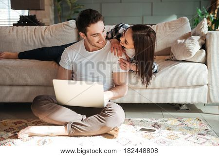 Full-length shot of young smiling man sitting with laptop on floor and his woman at sofa hugging him at home