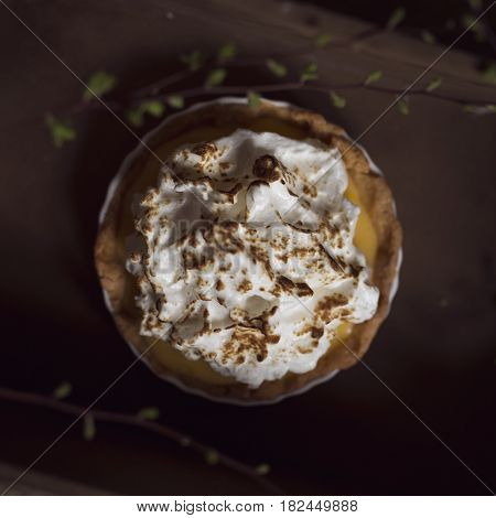 Top view of an apple tart decorated with whipped cream and cinnamon. Selective focus