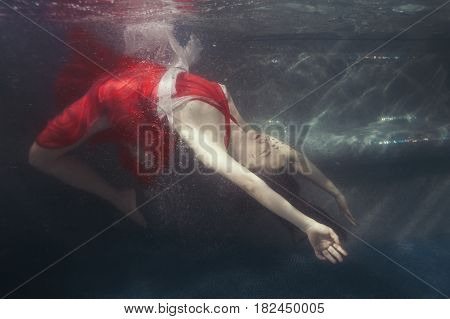 Woman dives under the water in a dress she is in the pool.