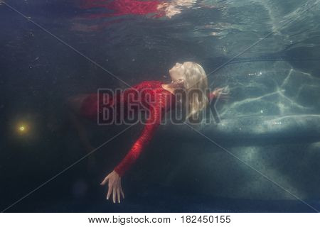 Blonde woman in a red dress under the water.