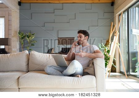 Smiling handsome man on sofa sitting with laptop while talking on phone