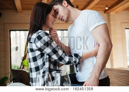 Brunette strong young man trying to kiss his pretty woman while she sitting on table