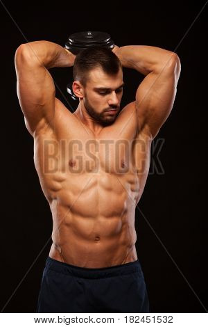 Strong man making exercises on triceps with a dumbbell. Close up shot training hands. Fitness Model showing his Torso with six pack abs. isolated on black background with copyspace.