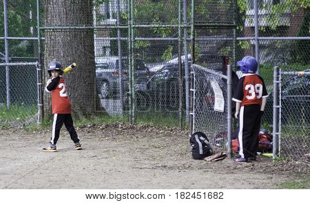 Montreal, Quebec - May 18, 2015 -- Wide view of little league baseball player looking at his team mate as he gets ready to swing the bat in a park in Montreal, Quebec on a bright day in Montreal.