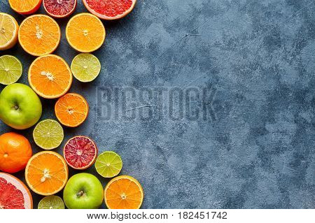 Citrus fruit mix on dark grey concrete table. Food background. Healthy eating and diet. Antioxidant, detox, dieting, clean eating, vegetarian, vegan, fitness or healthy lifestyle concept