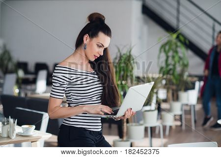 Attractive adult woman holding a laptop and typing a message to her subordinates to imform them about changes in schedule
