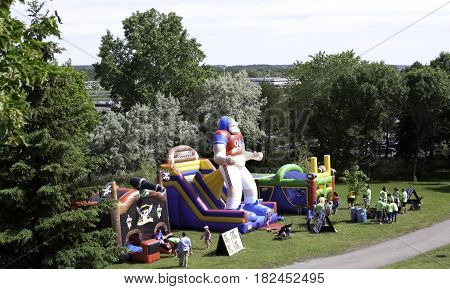 Laval, Quebec - June 14, 2015 - Landscape view of a large football themed blow up play equipment with a group of people waiting to jump inside at the
