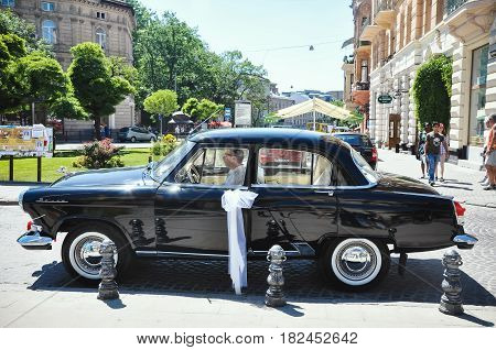 Lviv Ukraine - June 5 2011: Soviet car 60-xx years Volga GAZ-21. The driver expects young couple is crowned in the church.