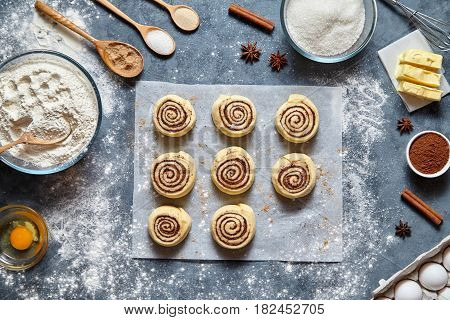 Cinnamon rolls or cinnabon homemade recipe raw dough preparation sweet traditional dessert buns pastry food baked homemade swirl Danish mini snack. Food ingridients flat lay on kitchen table. Top view