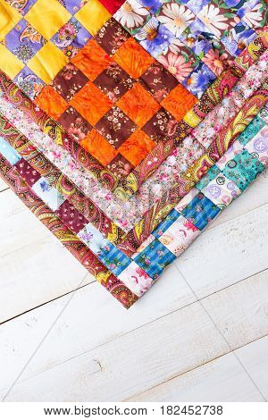 Part of symmetric geometry pattern color patchwork quilt on a white wooden background. Scrappy blanket with pattern of small squares. Handmade. Top view. Concept of handmade.
