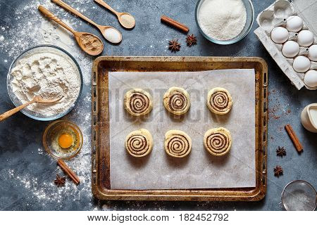 Cinnamon rolls or cinnabon handmade raw dough preparation recipe sweet traditional dessert buns pastry food baking sheet swirl Danish mini snack. Food ingridients flat lay on kitchen table. Top view