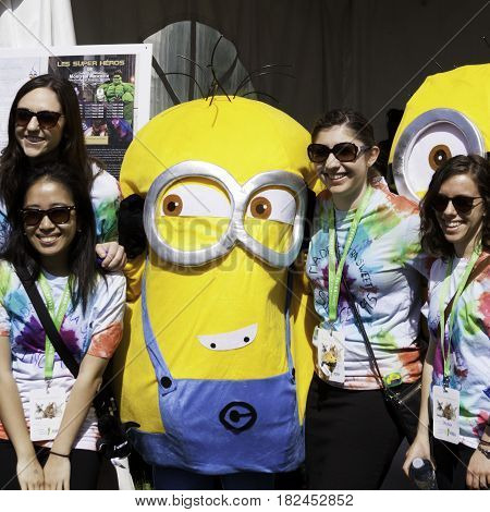 Laval, Quebec - June 14, 2015 - Square view of a large group girls posing with a costumed Minion at the