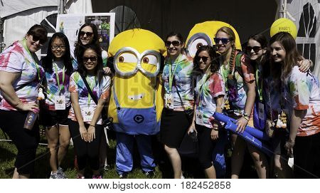 Laval, Quebec - June 14, 2015 - Landscape view of a large group girls posing with a costumed Minion at the