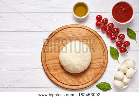 Raw pizza dough with baking ingredients on cutting board: dough, mozzarella, tomatoes sauce, basil, olive oil, cheese, spices. Italian margherita preparation on white wooden table. Italian pizza