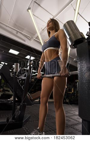 Sexy beautiful blonde in top and shorts exercising with barbell shot in sports gym