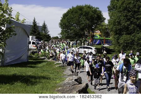 Laval, Quebec - June 14, 2015 - Landscape view of a large group of people starting down a path at the beginning of the