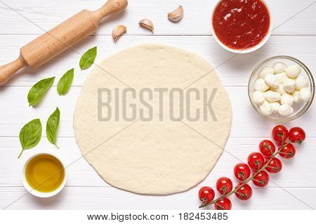 Pizza preparation. Baking ingredients on the kitchen table: rolled dough, mozzarella, tomatoes sauce, basil, olive oil, tomatoes, cheese, spices. Italian food cuisine background pizza margherita
