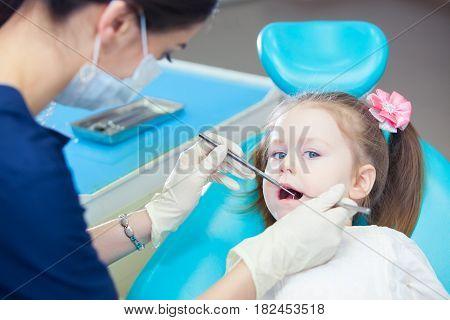 Little girl sitts in the dentist's office.