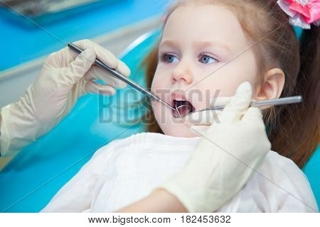Close-up of pretty little girl opening his mouth wide during inspection of oral cavity at the dentist.