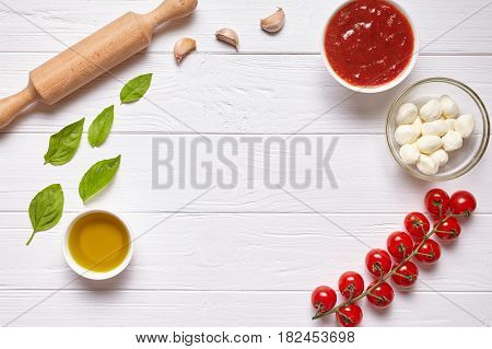 Rustic traditional Italian food background with empty copy design space on white wooden texture kitchen table. Basil, olive oil, tomato sauce, rolling pin, tomatoes. Flat lay, top view.