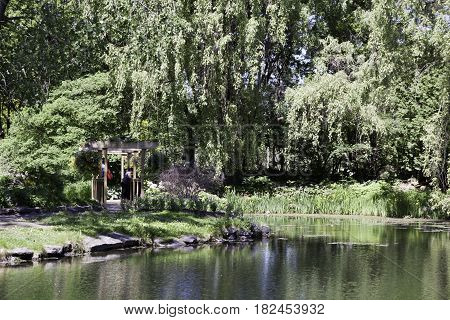 Laval, Quebec - June 14, 2015 - Landscape of a woman standing in a small wooden rest stop beside a man made lake in the Nature Park, Laval, Quebec on a sunny day in June.