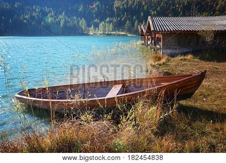turquoise alpine lake lautersee with moored rowing boat an boathouses in autumn
